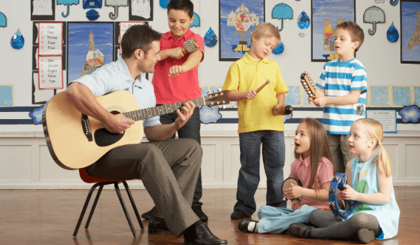 male teacher playing guitar with students