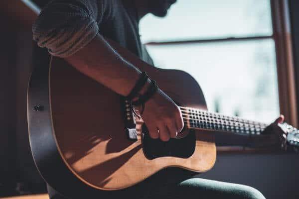 man playing guitar near window