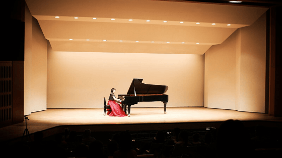 woman sitting on piano on stage