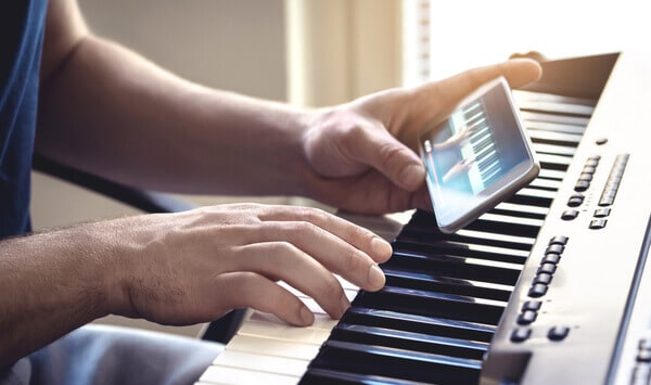man holding iphone next to piano