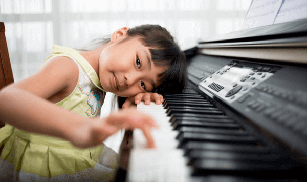 young girl playing at the piano displaying the benefit of learning piano at a young age